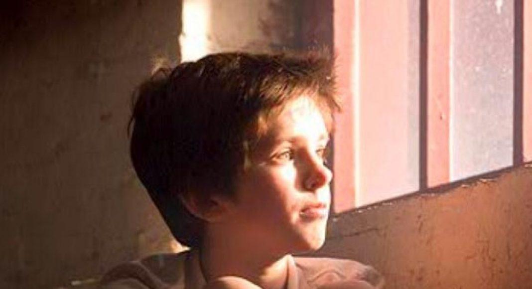 Dječak u sirotištu sklopio ruke i podigao oči u molitvi