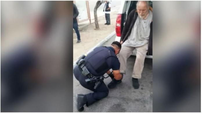policajac kleknuo beskućnik